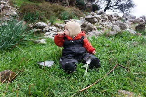 младенец играет с ложками и мисками