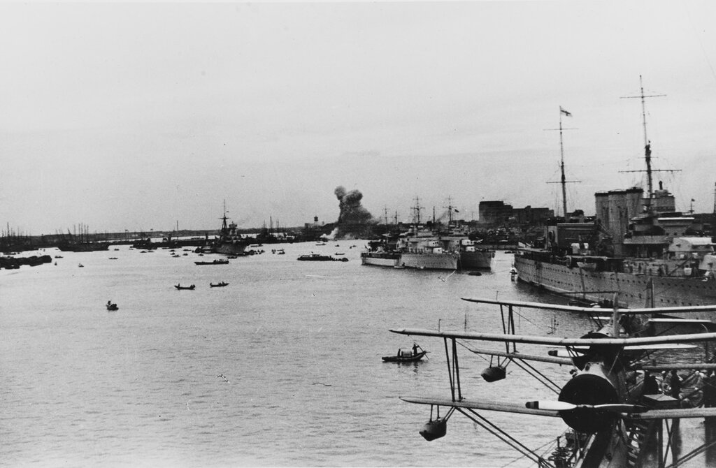 Shanghai, China. View looking upriver towards the Chinese suburb of Nantao, under Japanese bombardment. Ships in the river are (from left to right): RAIMONDO MONTECUCCOLI (Italian cruiser), DUMONT D'URVILLE and SAVORGNAN DE BRAZZA (French sloops), and HMS CUMBERLAND (British cruiser). Note Curtiss SOC aircraft on the USS AUGUSTA's (CA-31) catapult in the foreground and Vice Admiral's pennant at the mainmasthead of CUMBERLAND, circa the fall of 1937.