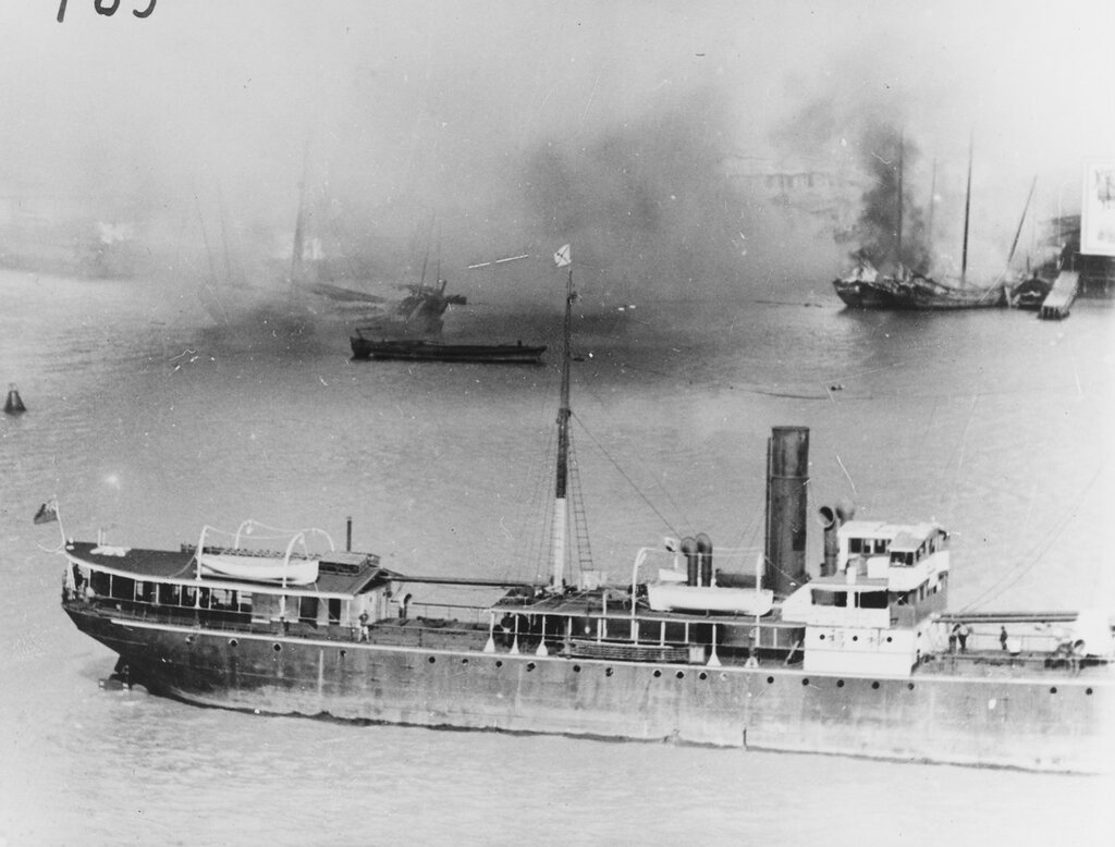 Shanghai, China. British river steamer heads upstream past burning waterfront buildings in Pootung Point, circa August 1937. View taken from USS AUGUSTA (CA-31).