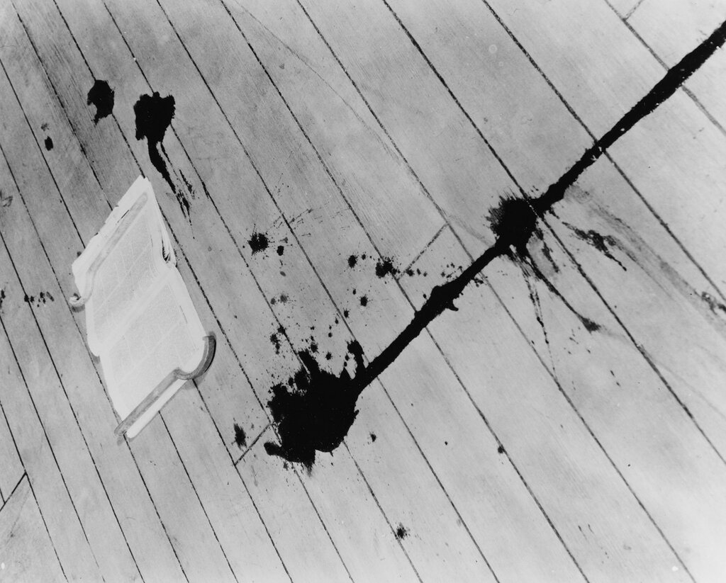 USS AUGUSTA (CA-31) Trail of blood on the deck from Seaman Second Class Freddie J. Falgout, killed by splinters from a Chinese antiaircraft shell on 20 August 1937. There were 17 men wounded by the same shell. The magazine that Falgout was reading while waiting for the movies to begin lies on the deck.