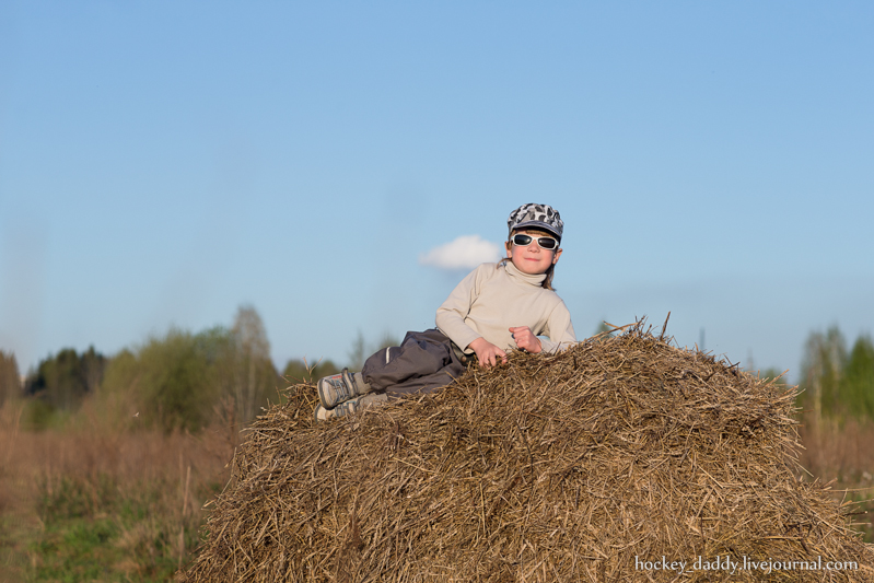 child sitting on a haystack