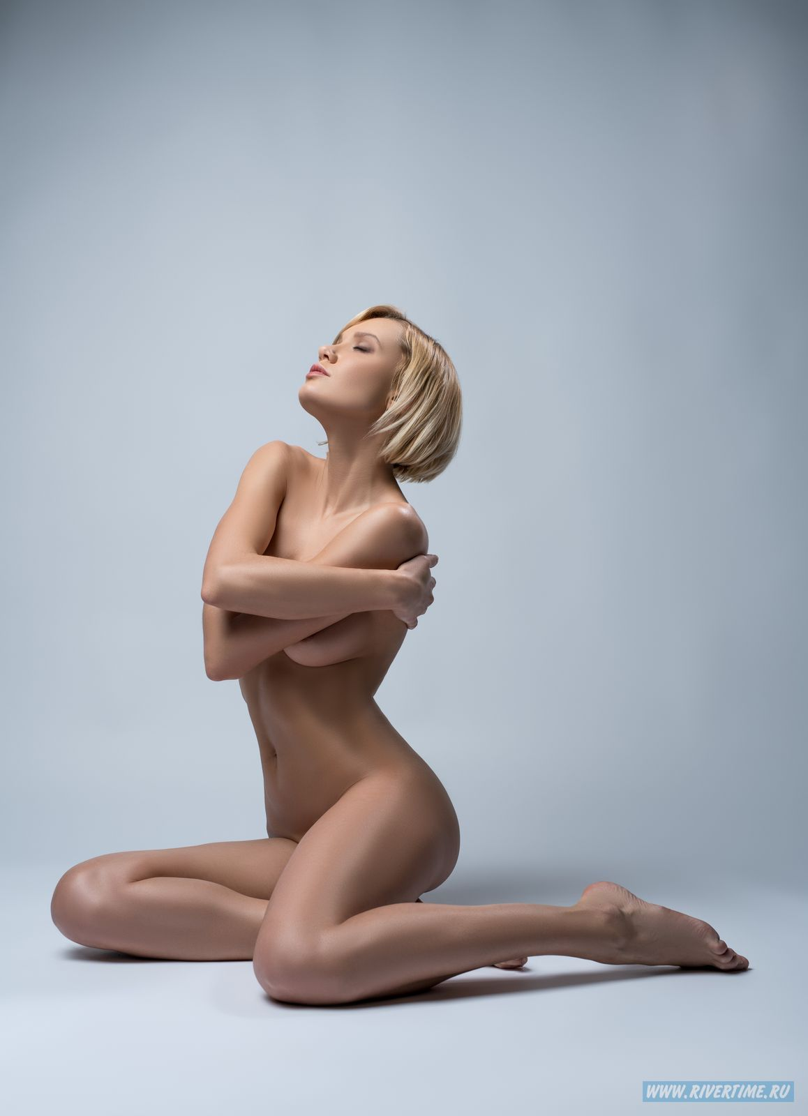 Image of naked blonde posing sensually at camera