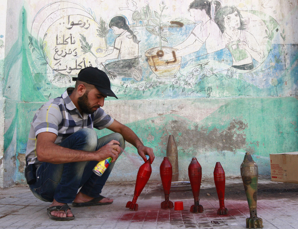 A Free Syrian Army fighter spray paints on improvised mortar shells at a weapon factory in Aleppo
