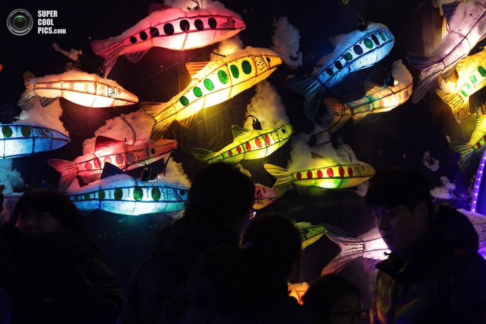 Посетители проходят мимо бумажных фонариков в виде форели. (Chung Sung-Jun/Getty Images)