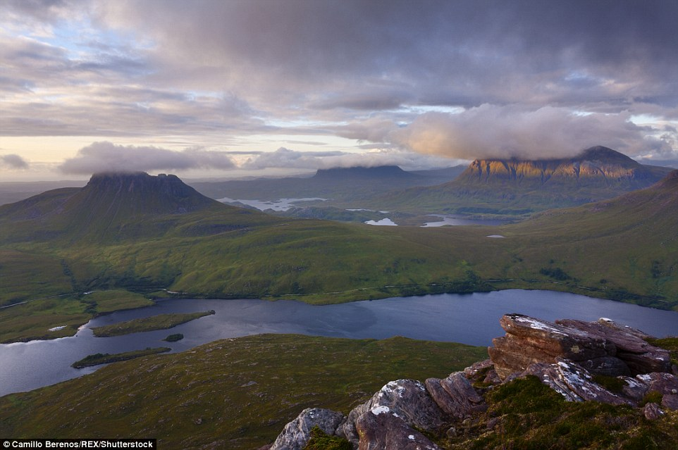Солнце восходит над горизонтом между горами Кул Мор и Кул Беаг на севере Шотландии.