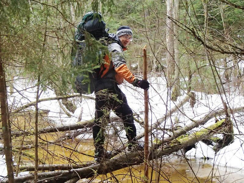 переправа через ручей по стволу в походе с рюкзаком
