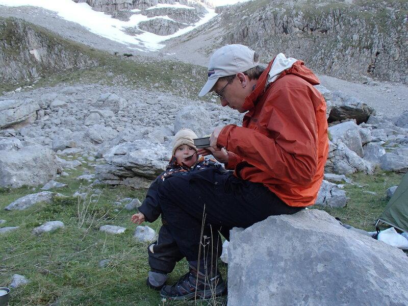папа кормит ребенка макаронами в горном походе