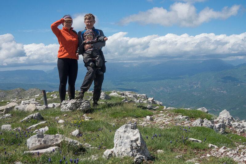 мама, папа и ребенок (1 год) на вершине горы в пешем походе по Греции