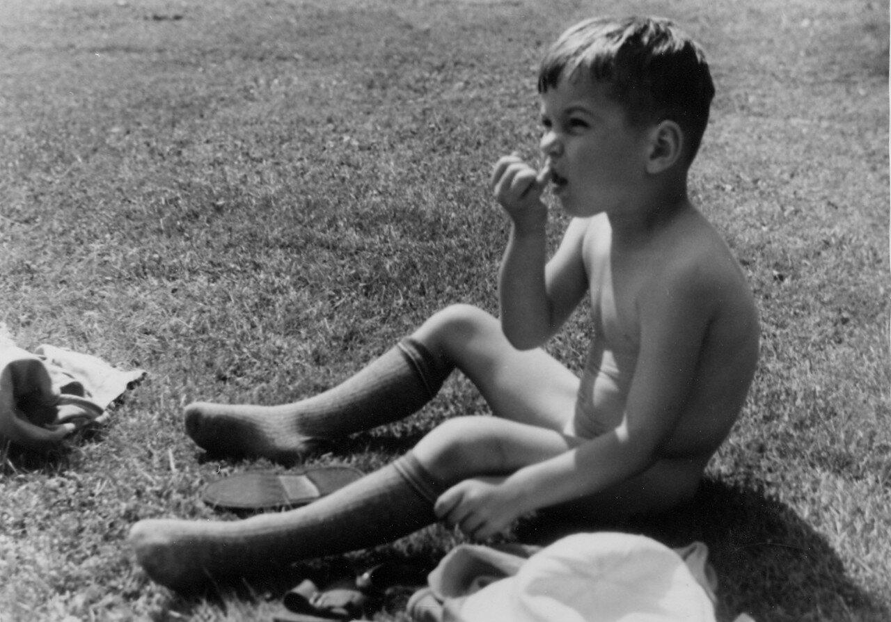 Голый мальчик сидит на лугу и ковыряет в носу