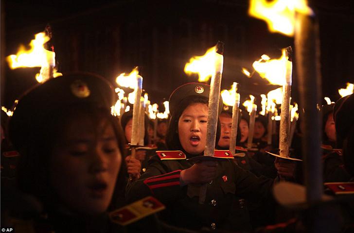 Участники молодежного движения идут в ногу с остальными и несут факелы.