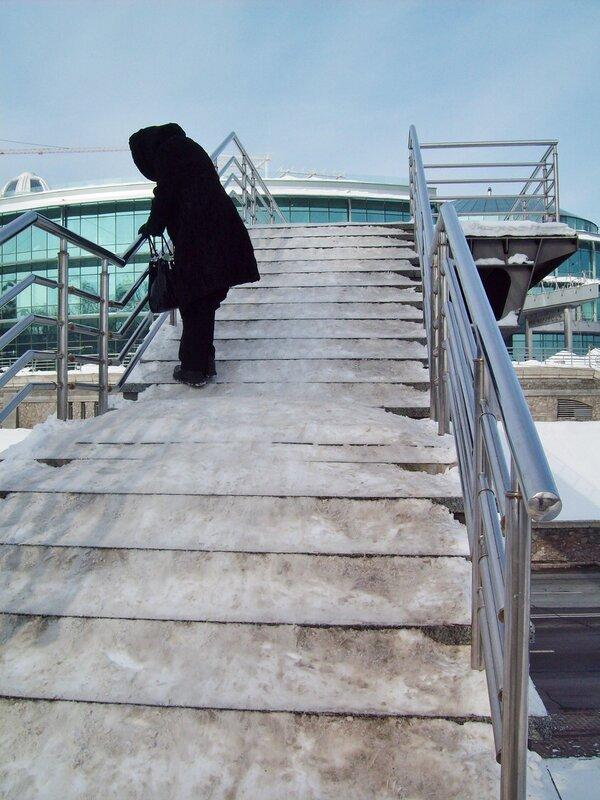Пешеход на мосту в парке Славы зимой