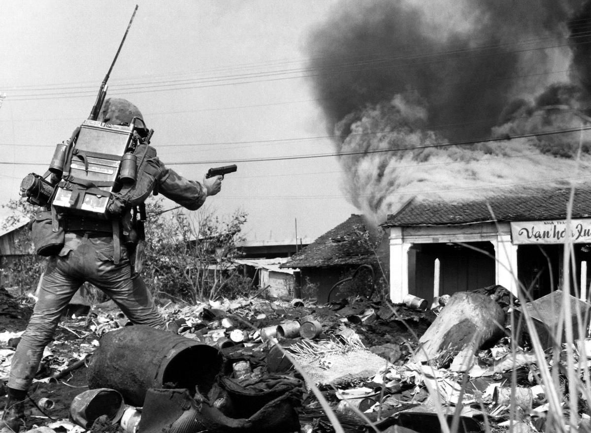 Южновьетнамский солдат, которыйпытается подобраться к горящему зданию на северо-востоке Сайгона, подожженному в результате атаки партизан на некоторые из кварталов этого города (19 февраля 1968 года)