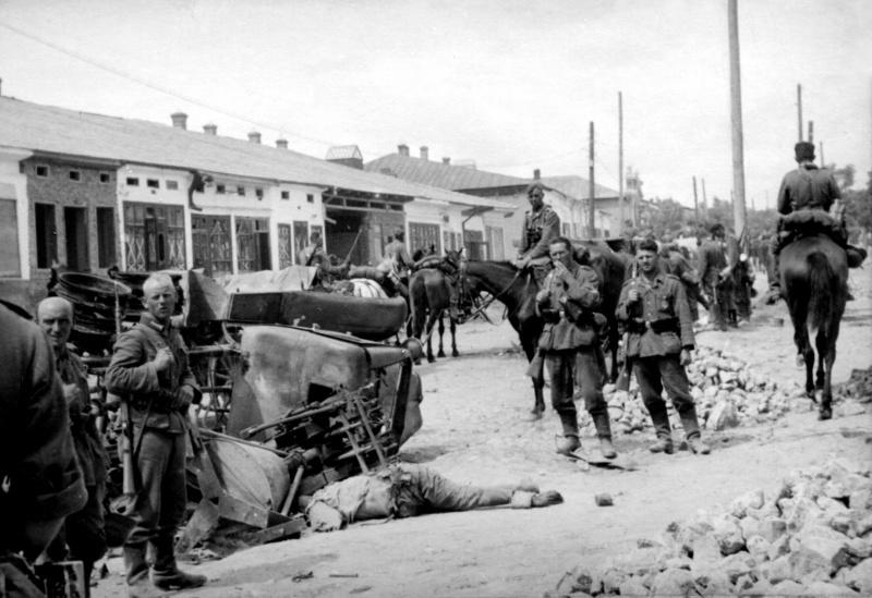 Немецкие солдаты рядом с телом погибшего красноармейца и разбитым грузовиком.jpg