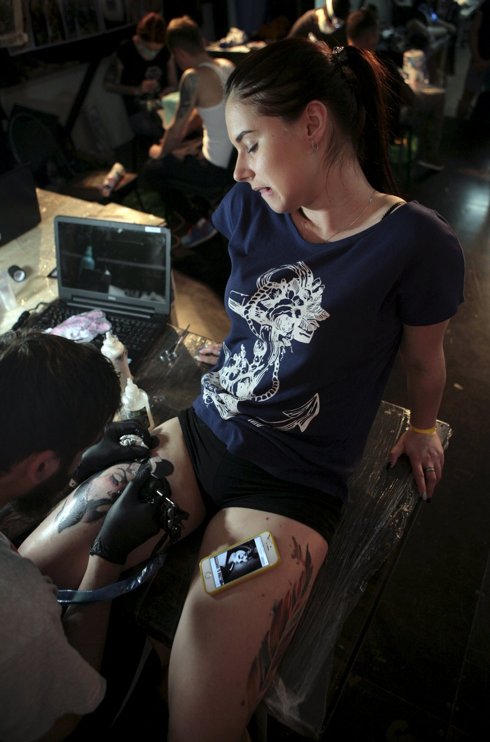 Artist works on tattoo on woman during International Tattoo Festival in Sochi