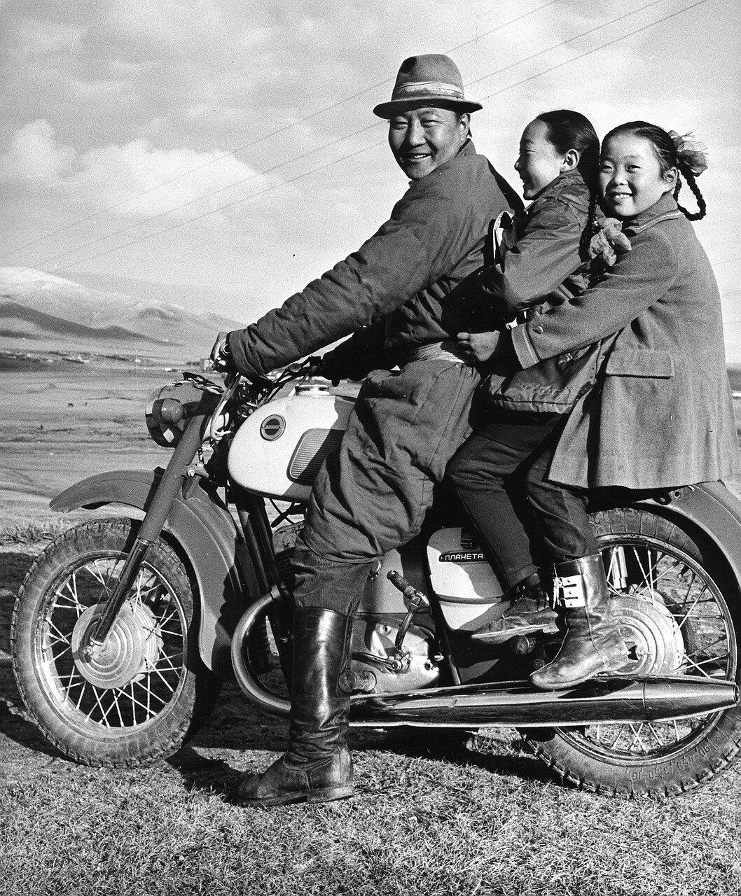 Поселок в степи. Отец с двумя дочерьми на мотоцикле