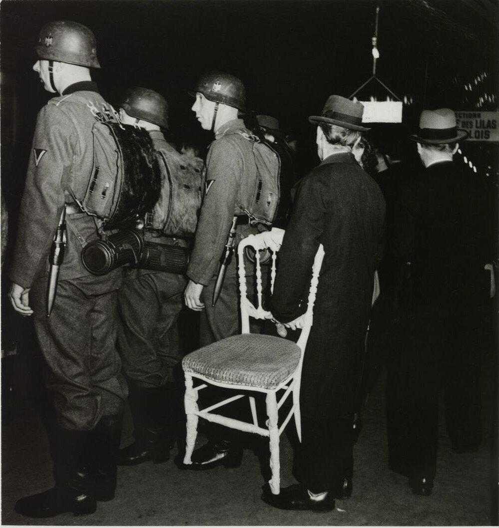 Немецкие солдаты и мужчина со стулом на платформе станции метро Порт де Лила