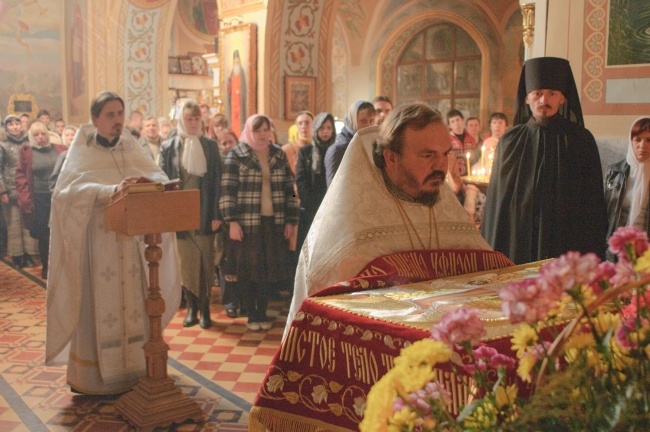Благочинный протоиерей Александр Устименко поднимает Св. Плащаницы для выноса в алтарь.