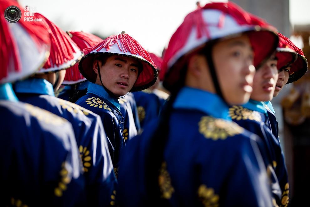 Китайские актеры, одетые в костюмы слуг династии Цин, репетируют свой номер. (AP Photo/Andy Wong