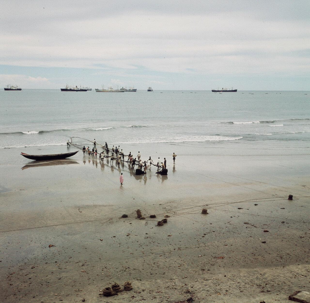 Растягивание рыболовной сети на берегу. На заднем плане грузовые суда, стоящие на якоре. 28 марта