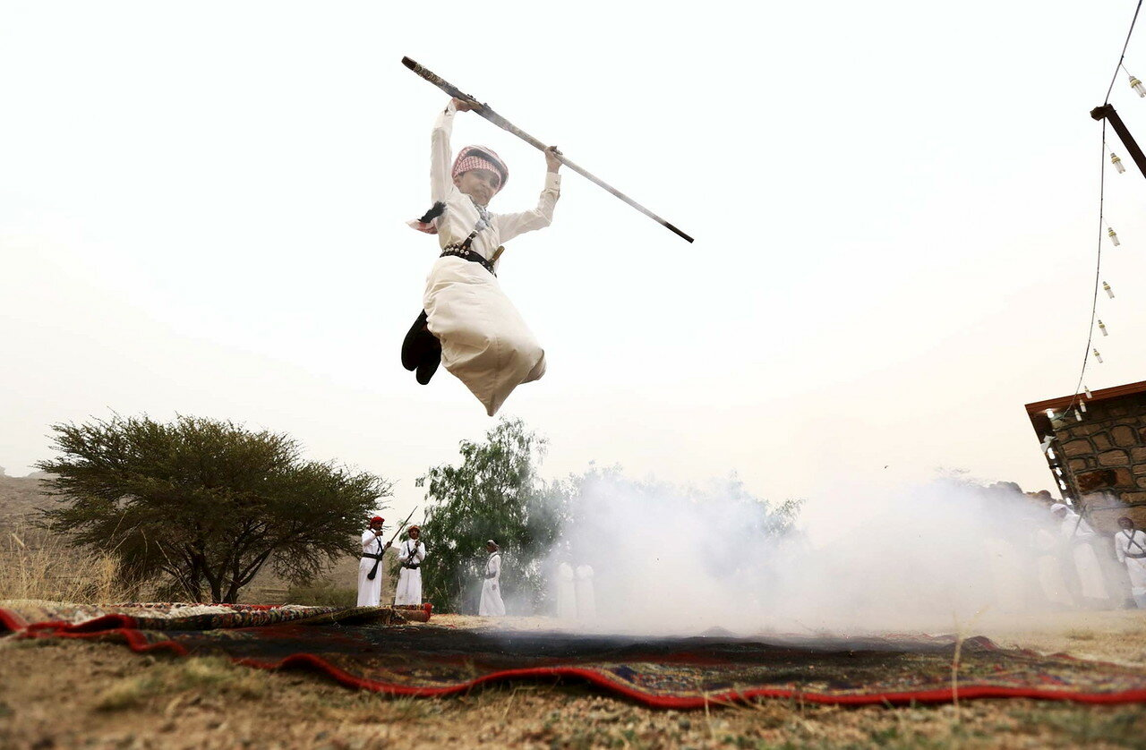 Boy fires a weapon as he dances during a traditional excursion near the western Saudi city of Taif