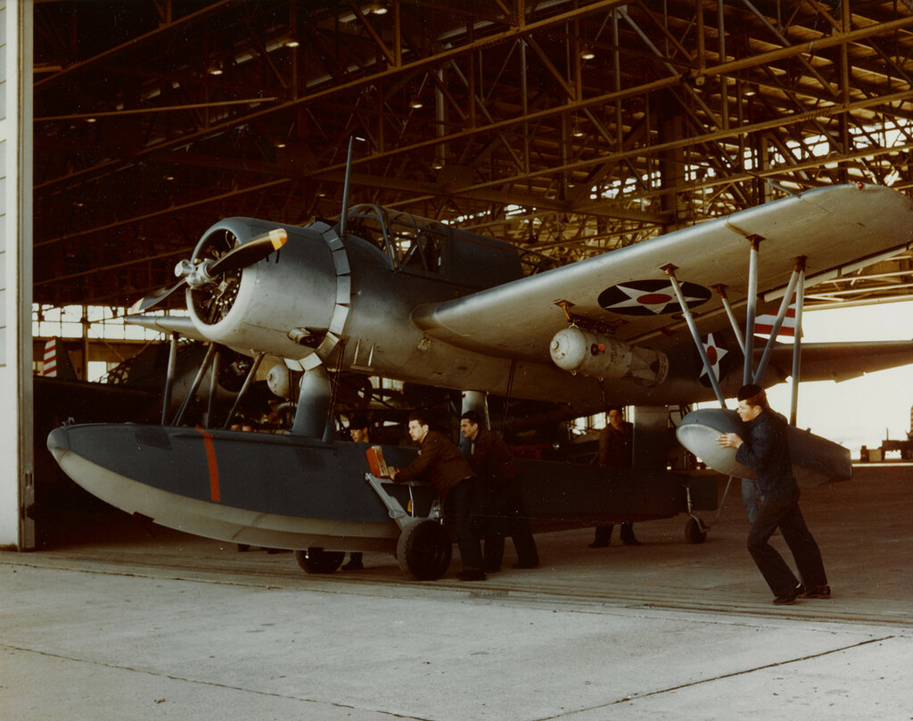 Men roll a Vought OS2U KINGFISHER Floatplane out of its hangar at a Naval Air Station, circa January - May 1942