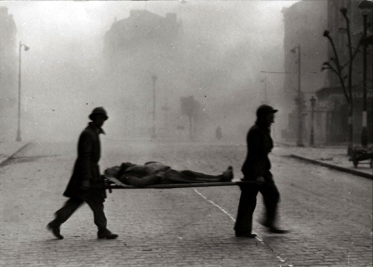 Апрель. Два спасателя, несущие раненого на носилках после бомбардировки Парижа союзниками
