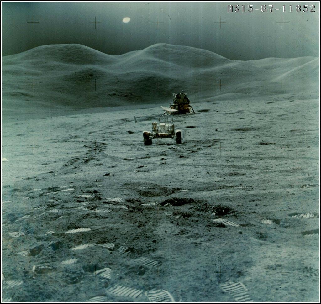 Уже подъезжая к «Фалкону», Скотт и Ирвин сообщили Хьюстону, что лунный грунт непосредственно вокруг лунного модуля — заметно светлее, чем поодаль, а их следы на нём, наоборот, тёмные. На снимке: «Фалкон» и «Лунный Ровер»