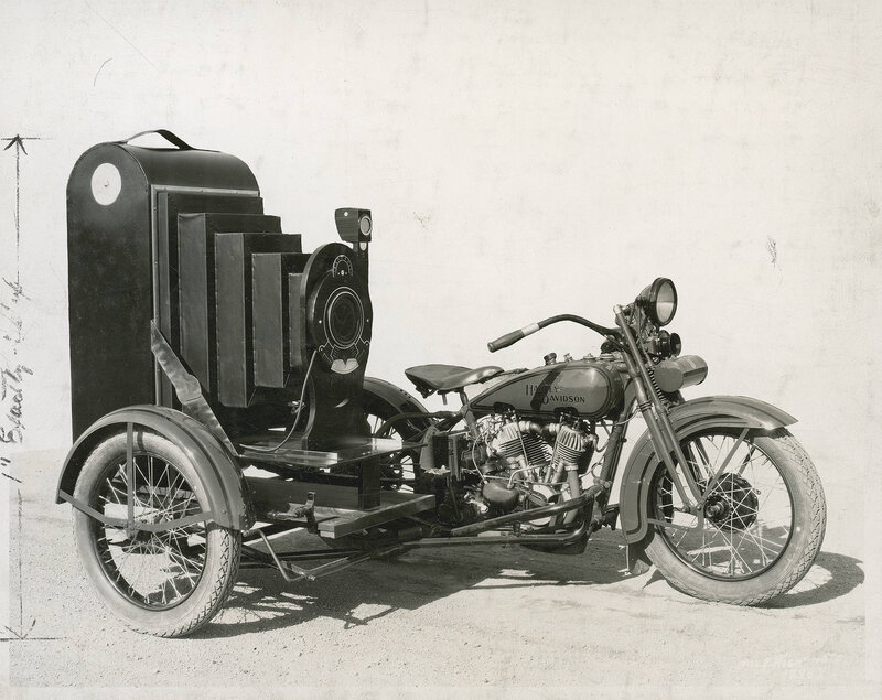 Harley Davidson motorcycle with a Winter-Weiss Company platform sidecar. An advertising model of an oversized folding bellows camera is on the sidecar's platform