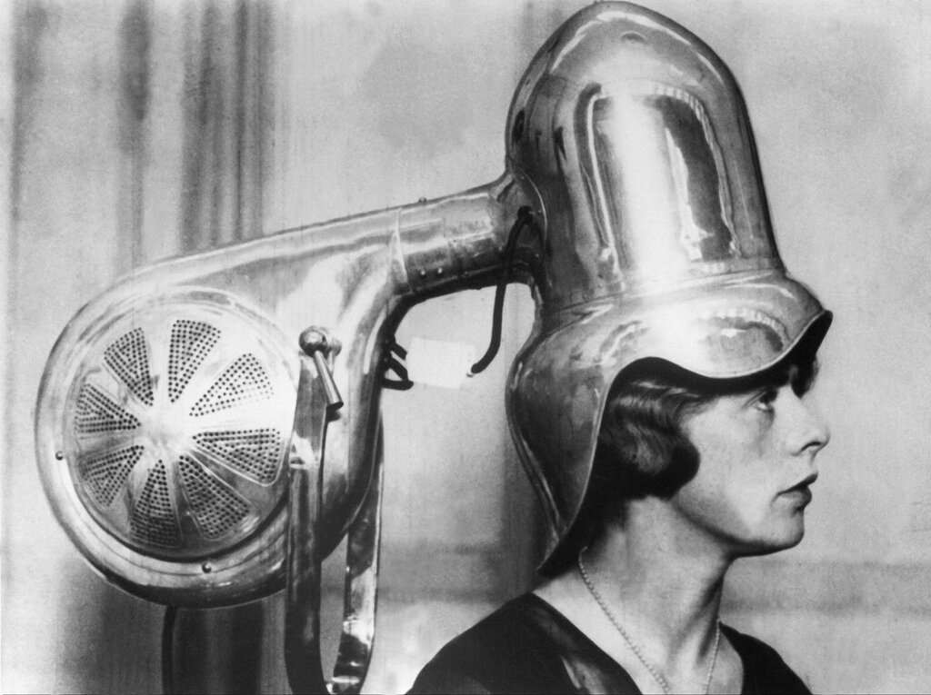 A woman sits under a chrome-plated hair dryer 1928.jpg