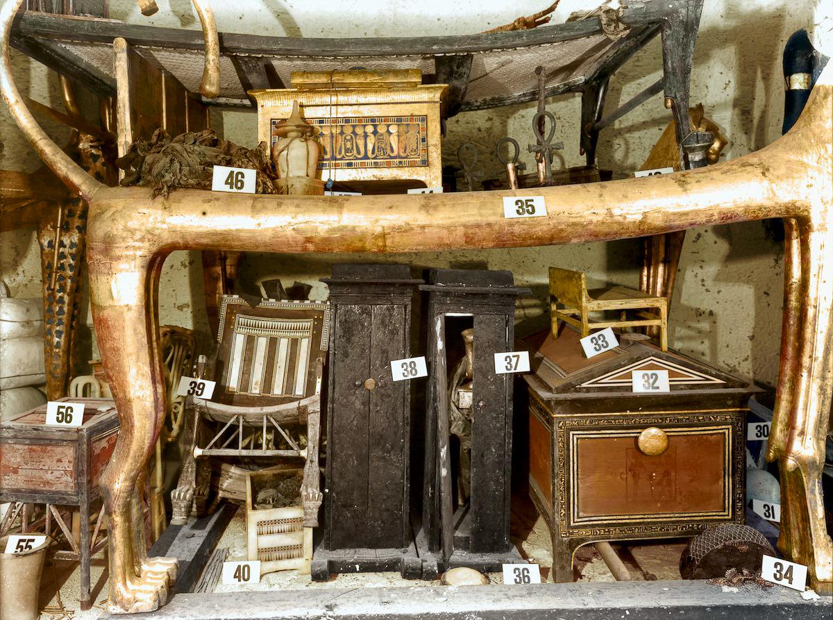 Под кроватью в форме льва несколько коробок, ящиков и кресло из чёрного дерева и слоновой кости, кот