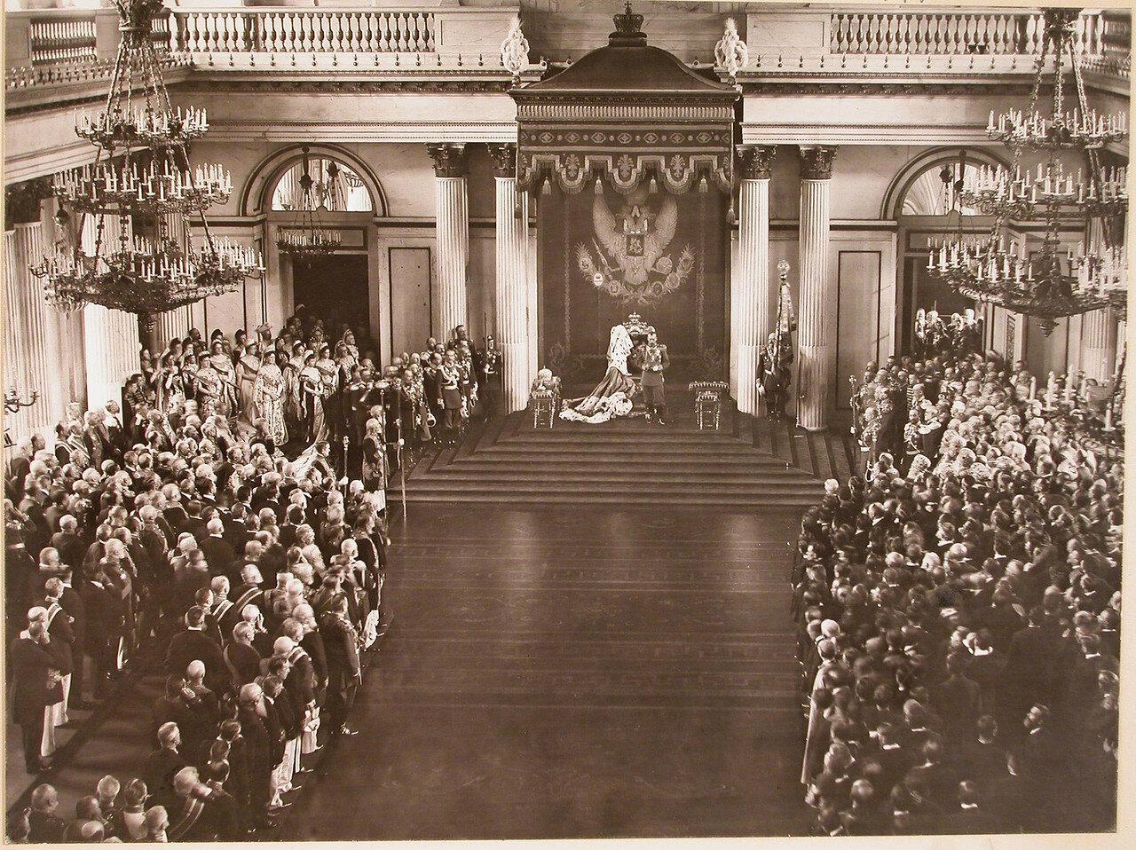 Император Николай II читает приветственное слово в день открытия I Государственной Думы в Георгиевском зале Зимнего дворца; слева (среди женской свиты великих княгинь, статс-дам, фрейлин) императрица Александра Федоровна