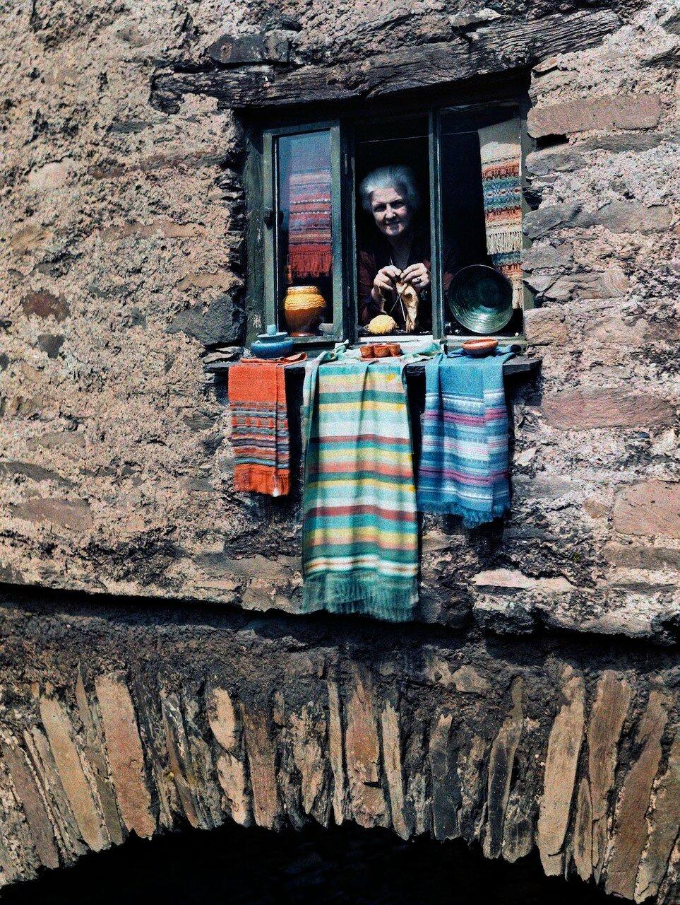 Женщина выглядывает из окна каменного дома в Эмблсайд, Лейк-Дистрикт (Озёрный край), Камбрия, Англия