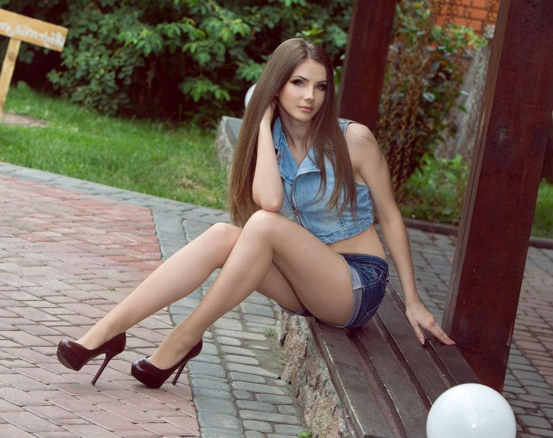 Длинноволосая девчонка  в мини шортах на каблуках