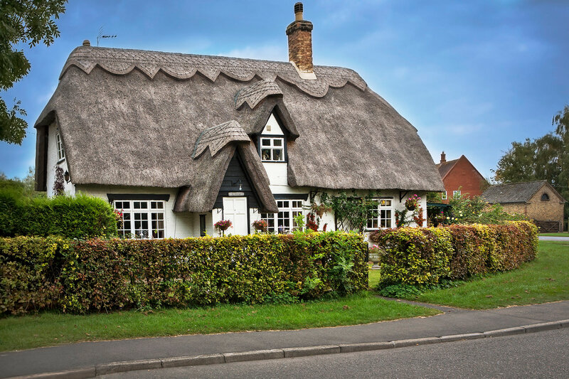 Charming thatched roof house in the Cotswolds English countryside.