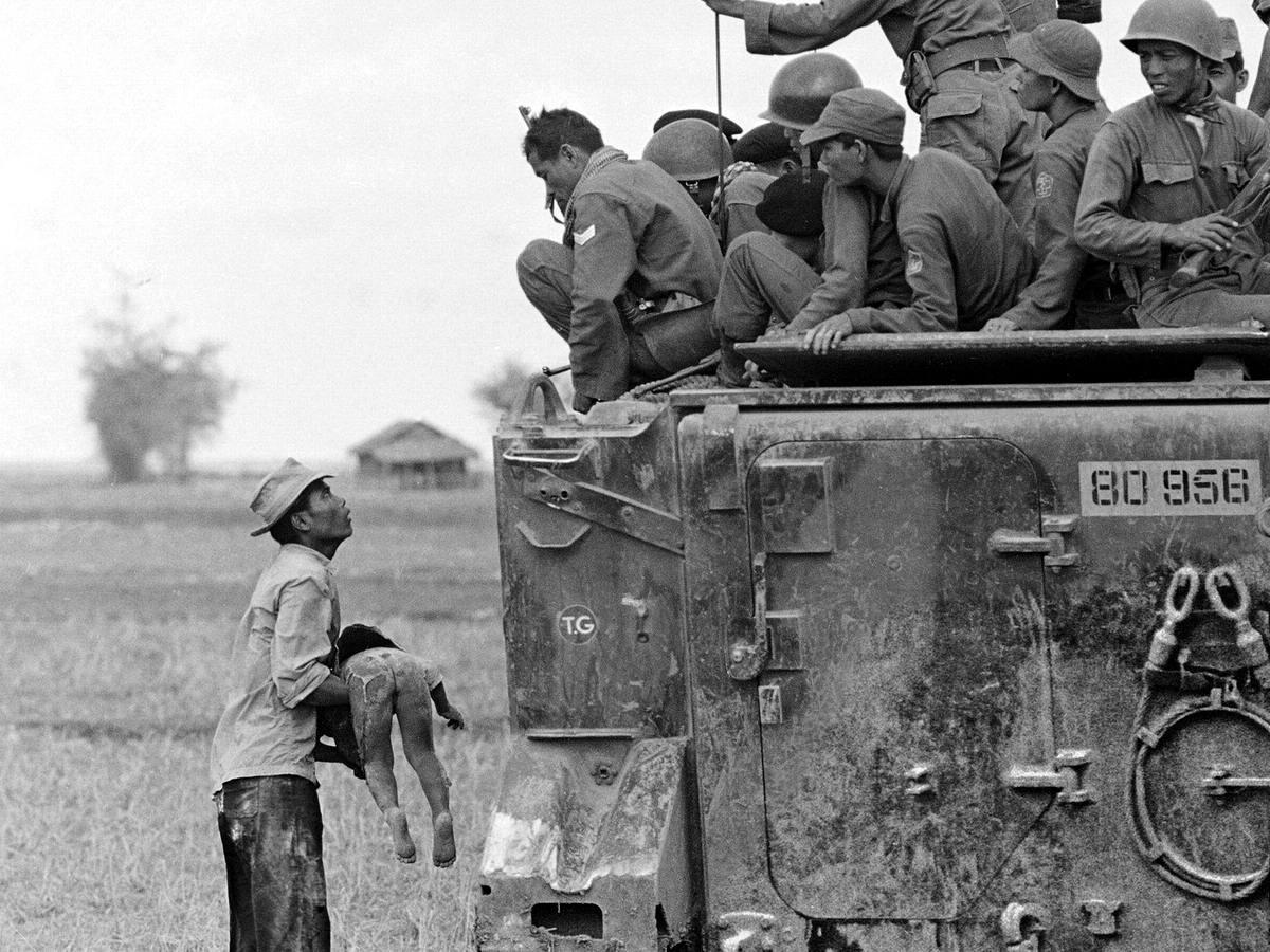Отец держит тело своего убитого ребенка перед южновьетнамскими рейнджерами, смотрящими на него с бронетранспортера (19 марта 1964 года)