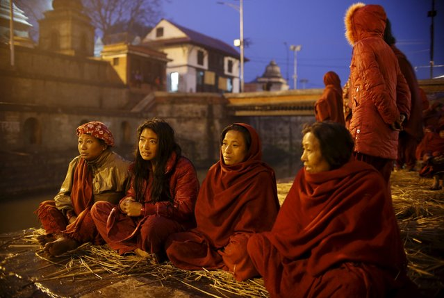Devotees gather near the bank of the Bagmati River at Pashupatinath Temple to offer prayers during t