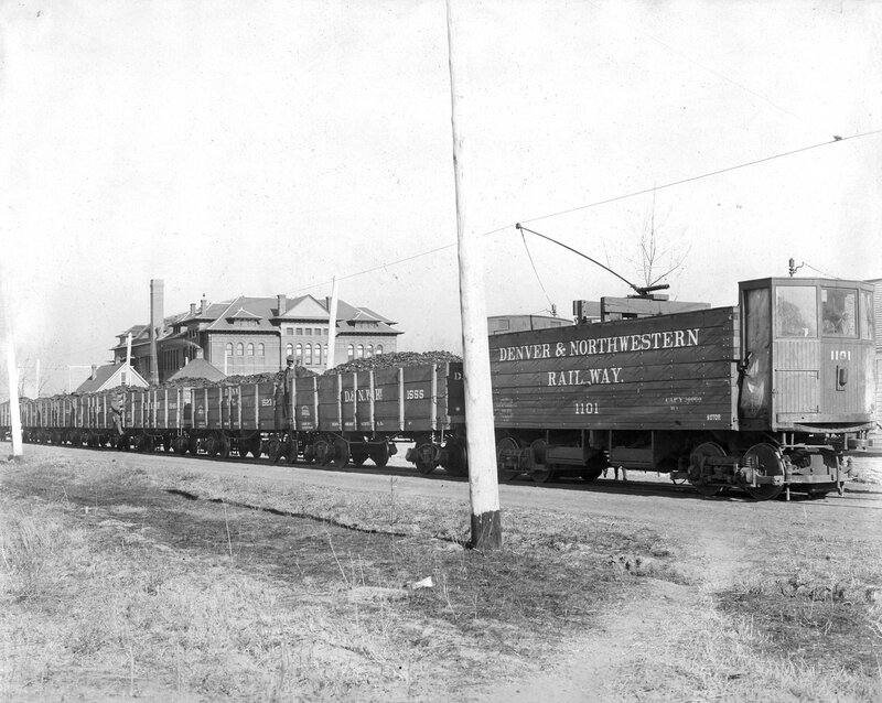 Leyden Mine coal trains, Denver & Northwestern Railway cars number 1101, 1555, 1523, and 1546 with Alcott Public School at West 41st (Forty-first) Avenue and Tennyson Street, Denver, Colorado in background, between 1900 and 1905