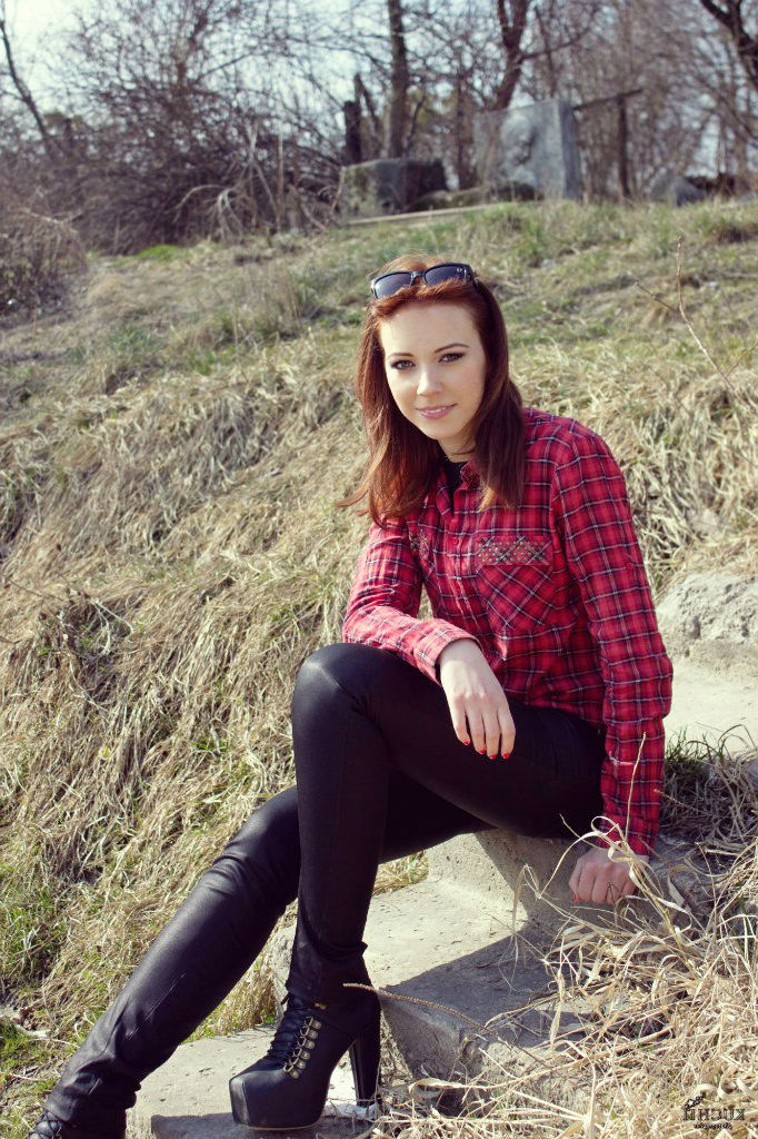 Рыжеволосая красотка на ступеньках кожаных брюках