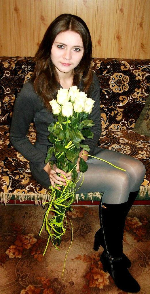 Темноволосая шатенка с букетом роз на диване