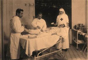 Врач,санитар и старшая сестра офицерского лазарета Л.В.Никитина за перевязкой раненого.