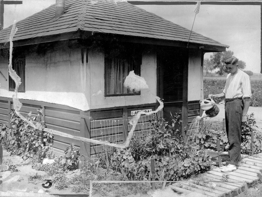 A man waters a flower garden at the Craig Colony (Craig Hospital) a tuberculosis sanitarium in Edgewater (Jefferson County), Colorado. A sign on a small building reads 'Arvada'. between 1916 and 1925
