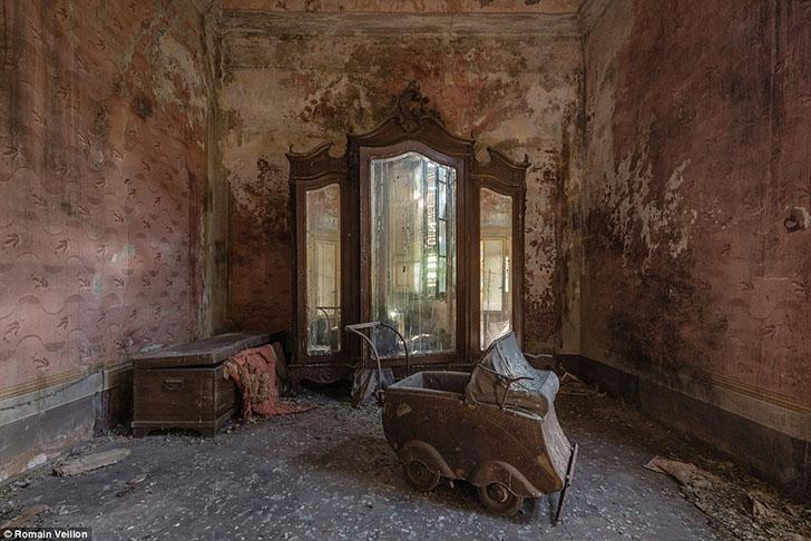 Коляска, сундук и гардероб с зеркалами в заброшенном доме в Италии.