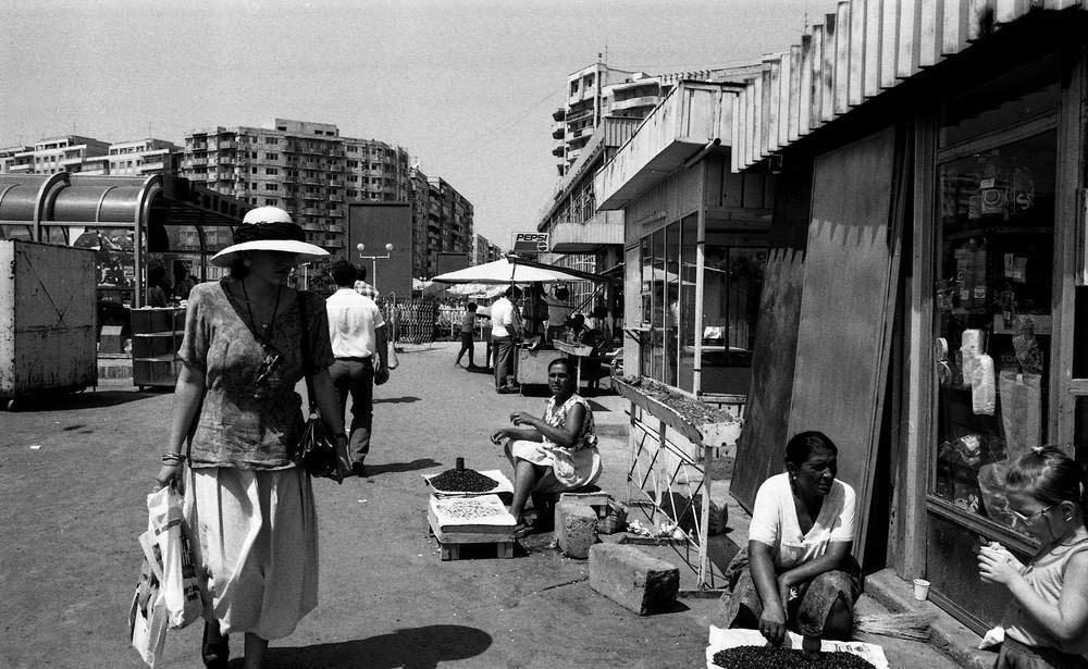 Цыганка продает жареные семечки у входа на рынок.