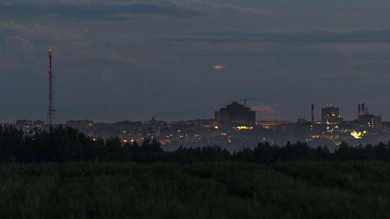 Телебашня, строящийся жилой комплекс Алые паруса и трубы ТЭЦ-4 и Биохима ночью с противоположного берега реки Вятки