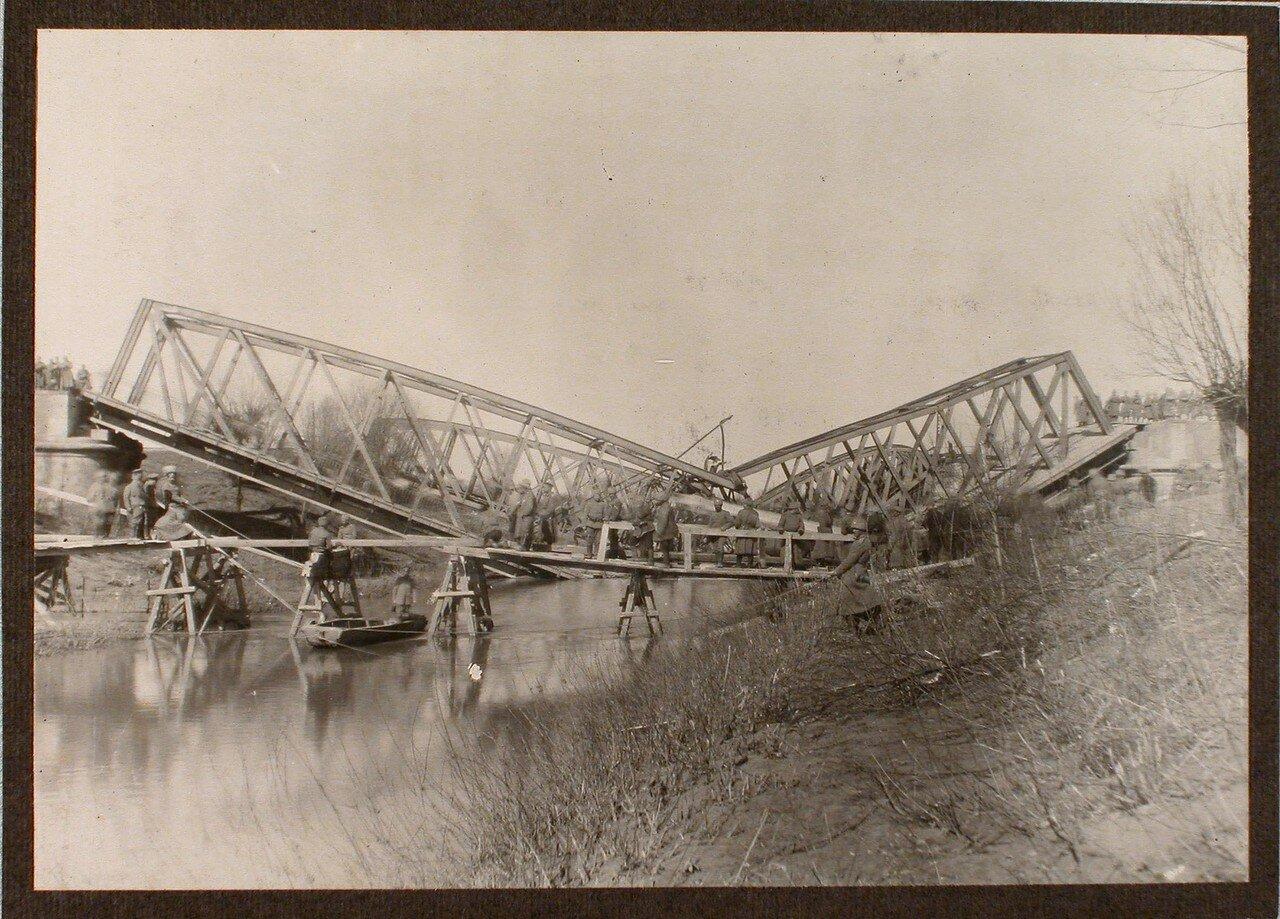 13. Бойцы саперной роты наводят временный мост через реку Виар; на втором плане - взорванные мосты