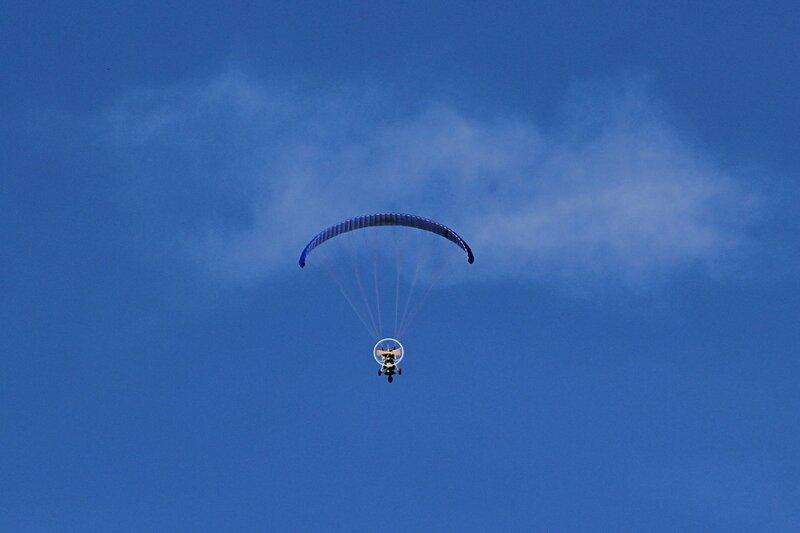Паралёт (аэрошют, мотопараплан со специальной тележкой) в небе над Кировом. Параплан (парашют-крыло) с двигательной установкой с пропеллером