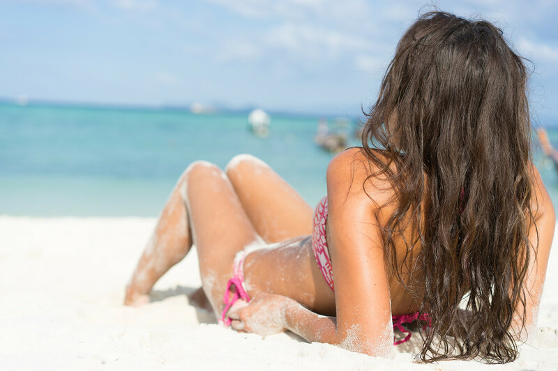 Tropical vacation. Young beautiful woman on the beach. Back view.