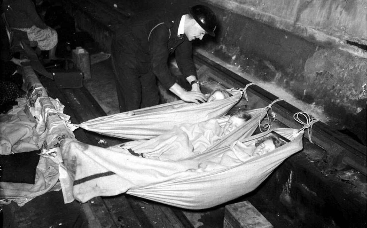 1940. Во время воздушной тревоги командир отряда гражданской обороны проверяет детей спящих в подвесных койках, натянутых между рельсами