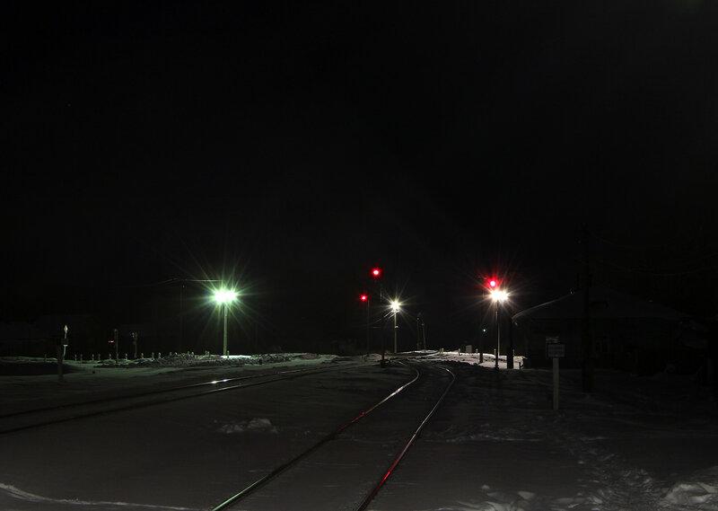 Переезд и чётные прожекторные выходные светофоры на станции Высокое, вид на Торжок