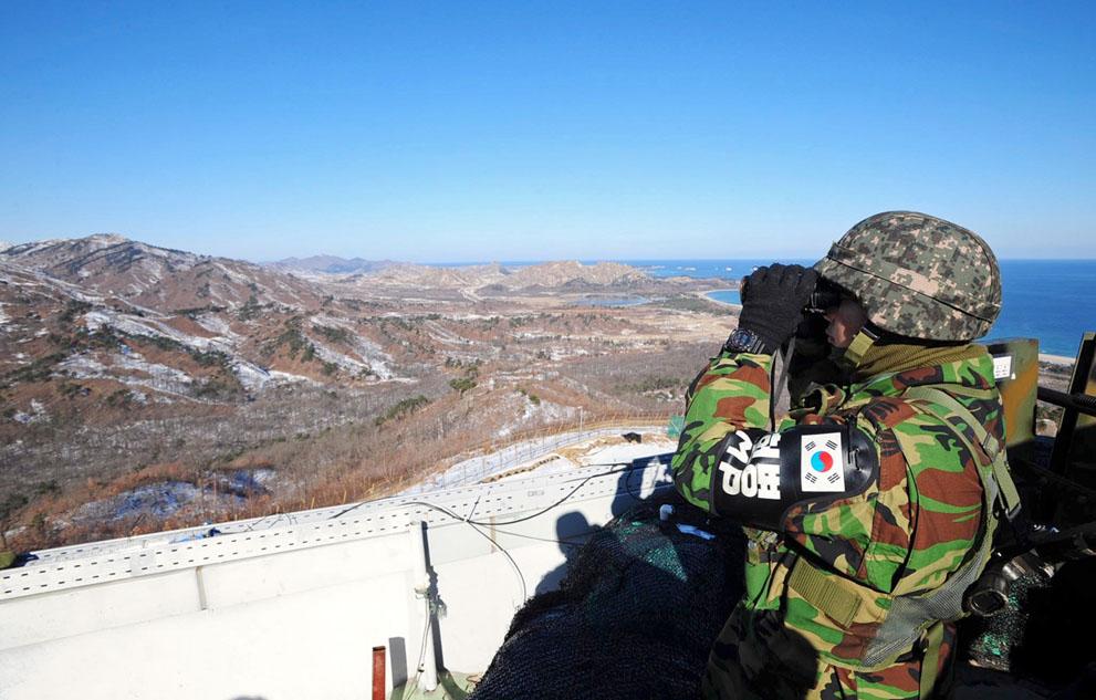 31. Южнокорейский солдат смотрит в бинокль на сторону Северной Кореи после новостей о кончине Ким Че